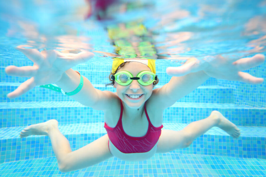 Happy girl in swimming glasses under water in the pool