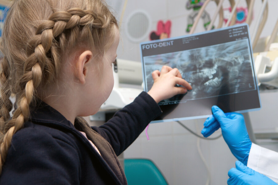 Doctor showing female child safe x-rays during exam