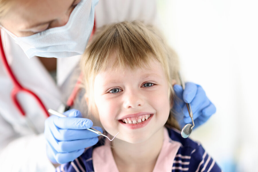 dental hygienist Portrait of smiling girl at dentist appointment. Treatment of baby milk teeth concept